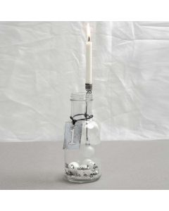 A Bottle with a decorated Candle Holder and a Metal Sign
