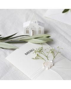 A menu card in off-white shades with a punched-out church and vellum paper
