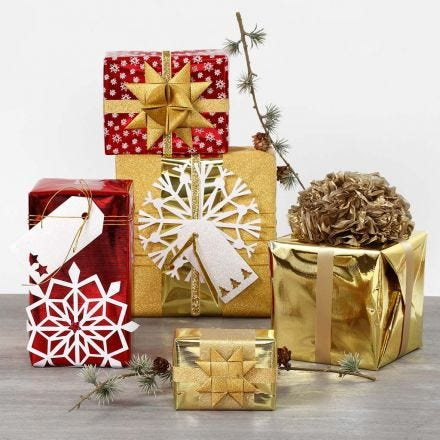 Gift Wrapping with metallic Wrapping Paper and shiny Decorations