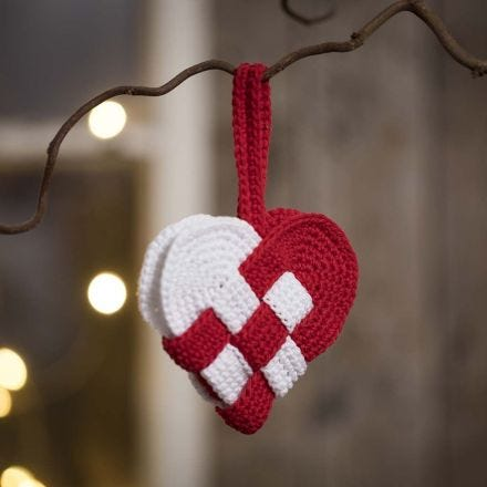 A crocheted woven Christmas heart basket from red and white cotton yarn