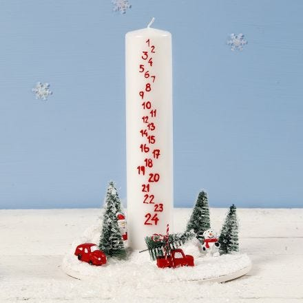 A Decoration with an Advent Candle surrounded by a Miniature Christmas World