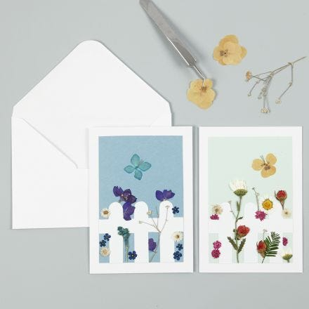 A Greeting Card with dried Flowers behind a Picket Fence