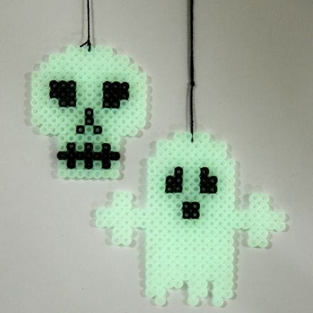 A luminescent Ghost and Skull made on a Pegboard