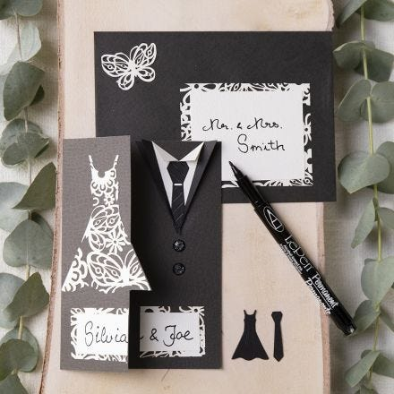 A wedding invitation decorated with a dress and a dinner jacket