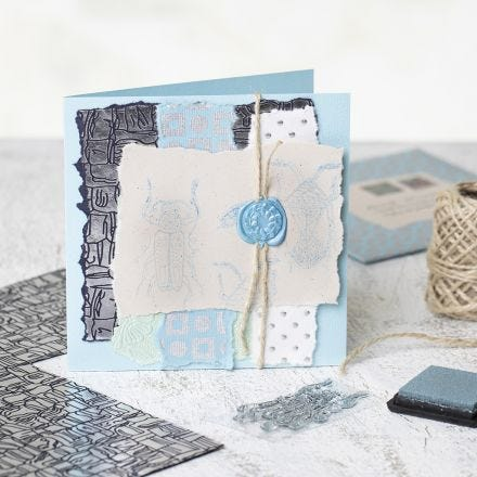 A homemade Greeting Card with handmade Paper, stamped Designs and a waxed Seal