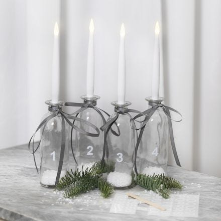An Advent candle holder from glass bottles with LED candles and rub-on stickers