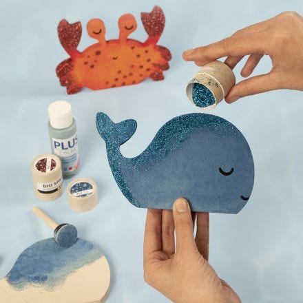 A whale and a crab decorated with craft paint and bio glitter