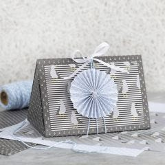 A dark blue Gift Box decorated with a blue Rosette and Design Paper