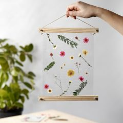 A hanging Decoration with laminated, dried Flowers in Poster Hangers
