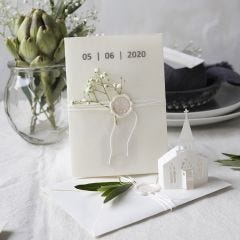 An invitation in off-white shades with a punched-out church and vellum paper