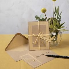An invitation from recycled card decorated with a skeleton leaf