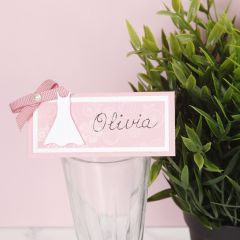A place card for a confirmation party decorated with a dress and a bow