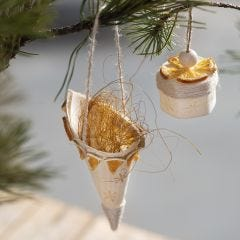 A wood veneer cone decorated with stamped designs and natural materials
