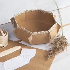 A faux leather paper basket with a crocheted raffia paper yarn edge