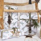 Christmas Gift Wrapping with a green Branches Motif, decorated with a Piece of Natural Hemp, Ribbon and Natural Bark Gift Tag