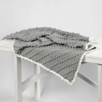 A crocheted Baby Blanket with diagonal Bobbles