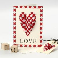 A Valentine Card with a sewn-on Paper Heart and stamped Text