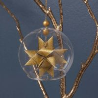 A clear Glass baseless hanging Bauble with a woven Star