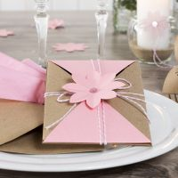 An Invitation wrapped and secured with Cotton Cord and a punched-out Flower