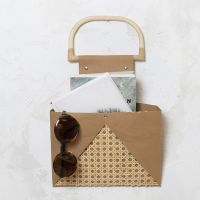 Wall mounted storage from faux leather paper and rattan