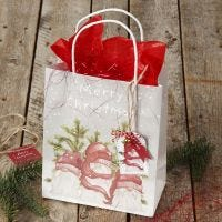 Christmas gift wrapping with a  gift bag and gift tag with a bell