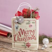 A gift bag with a Christmas design, decorated with a star, lametta and tissue paper