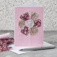 A greeting card with a sewn-on fabric flower design
