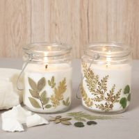 Rapeseed wax candles in a glass lantern decorated with dried flowers